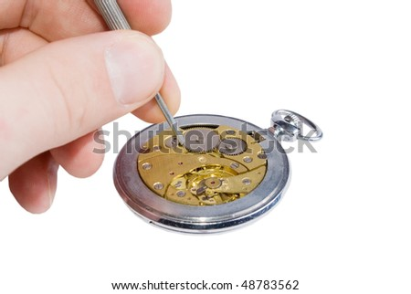 Hand holding a watch screwdriver and an old watch mechanism (isolated on white) - stock photo
