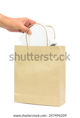 Hand holding a white box in brown paper shopping bag isolated white background - stock photo