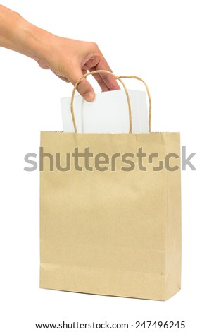 Hand holding a white box in brown paper shopping bags isolated white background - stock photo