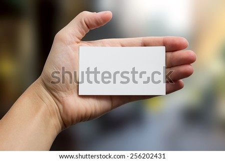 Hand holding a white business card on blurred background