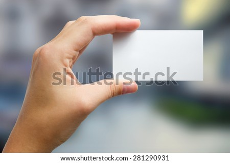Hand holding a white business visit card, gift, ticket, pass, present close up on blurred blue background. Copy space - stock photo