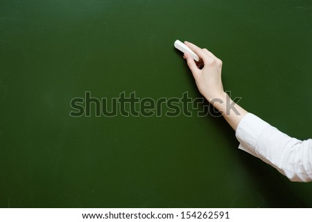hand holding a white chalk about to write - stock photo