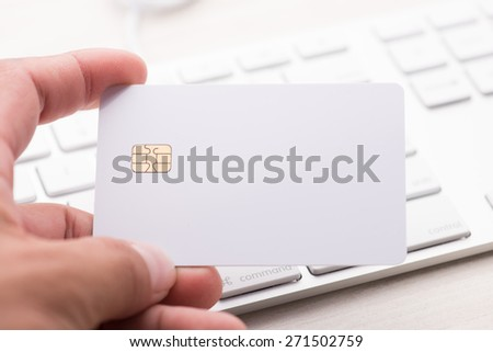 hand holding a white credit card and typing. On-line shopping on the internet - stock photo