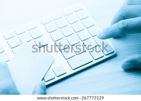 hand holding a white credit card and typing. On-line shopping on the internet in blue tone - stock photo