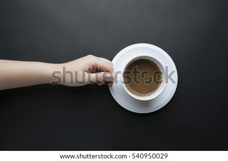 Hand holding a white cup of coffee on black background