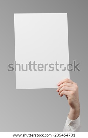 Hand holding a white paper blank isolated on grey background  - stock photo