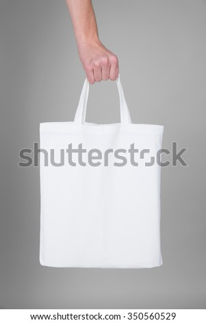 Hand holding a white textile bag -  usable as a mockup for your message - stock photo