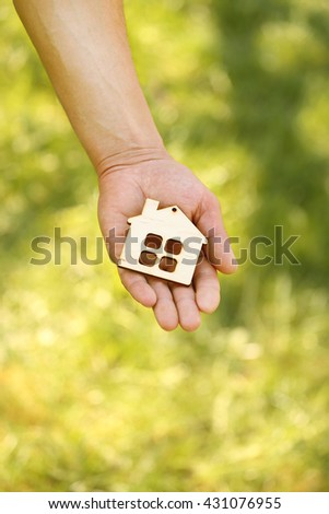 hand holding a wood house