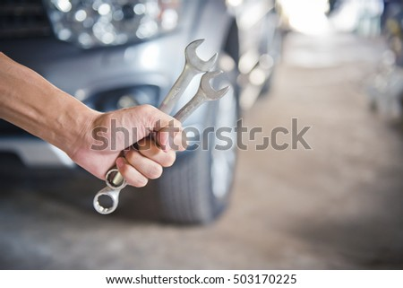 Hand holding a wrench with a car repairs ,professional auto mechanic