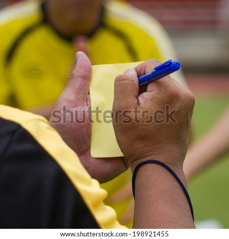 Hand holding a yellow card - stock photo