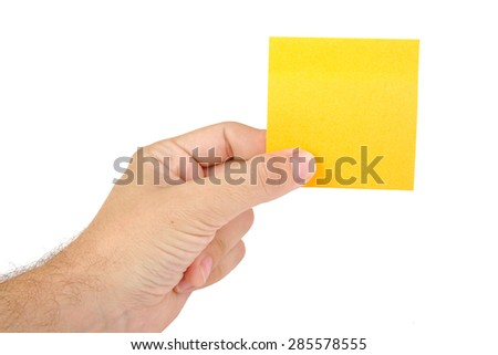Hand holding a yellow notepaper or postit isolated on white  background - stock photo