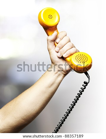 hand holding a yellow vintage telephone indoor