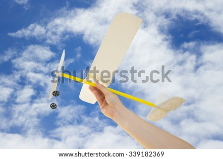 Hand holding airplane plane on Blue sky with clouds many cubes background - stock photo