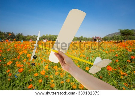 Hand holding airplane plane on orange cosmos flower background - stock photo