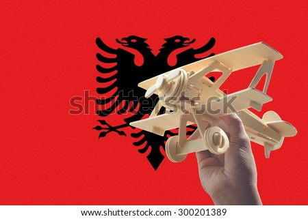 Hand holding airplane plane over Albania flag, travel concept - stock photo