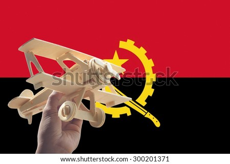 Hand holding airplane plane over Angola flag, travel concept - stock photo
