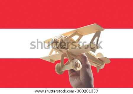 Hand holding airplane plane over Austria flag, travel concept - stock photo
