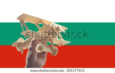 Hand holding airplane plane over Bulgaria flag, travel concept - stock photo