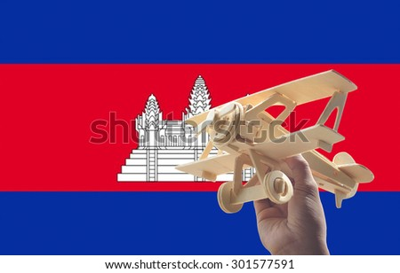 Hand holding airplane plane over Cambodia flag, travel concept - stock photo