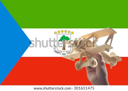 Hand holding airplane plane over Equatorial Guinea flag, travel concept - stock photo