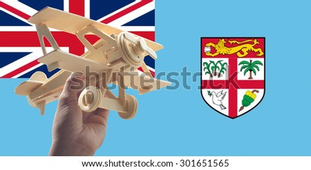 Hand holding airplane plane over Fiji flag, travel concept - stock photo