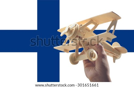Hand holding airplane plane over Finland flag, travel concept - stock photo
