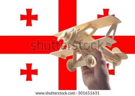 Hand holding airplane plane over Georgia flag, travel concept - stock photo