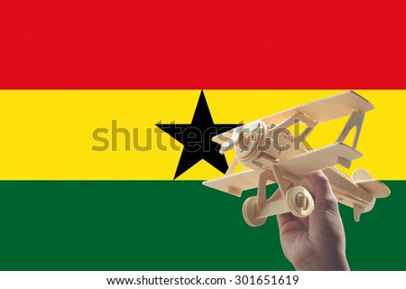 Hand holding airplane plane over Ghana flag, travel concept - stock photo