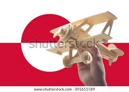 Hand holding airplane plane over Greenland flag, travel concept - stock photo