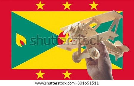 Hand holding airplane plane over Grenada flag, travel concept - stock photo
