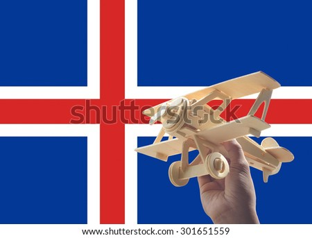 Hand holding airplane plane over Iceland flag, travel concept - stock photo