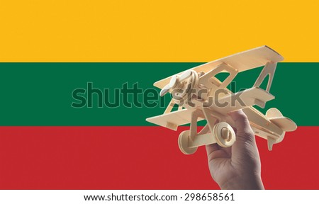 Hand holding airplane plane over Lithuania flag, travel concept - stock photo