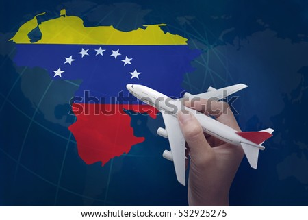 hand holding airplane with map of Venezuela.