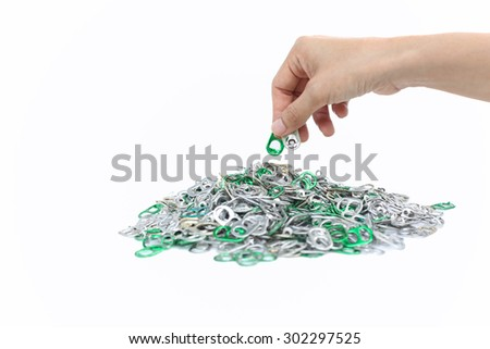 Hand holding aluminum cap can over a pile of cap can in white background - stock photo