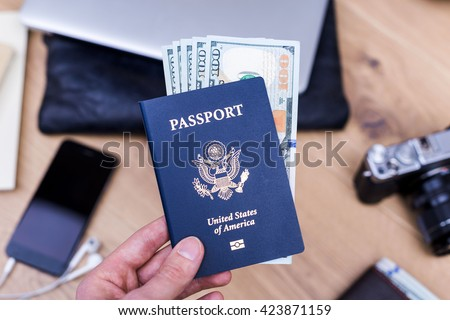 Hand holding american passport with dollars over desktop with smart phone, camera, purse and other items. Traveling concept