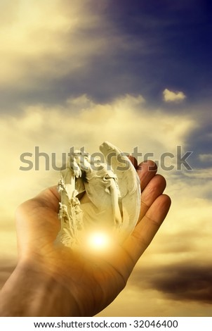 hand holding an angel with divine light - stock photo