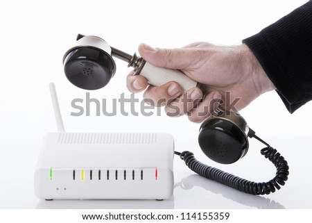 Hand holding an antique telephone phone that is connected to a wireless router with the lights on - stock photo