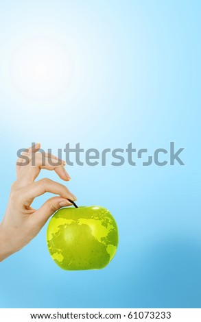 Hand holding an apple with a map of the earth - stock photo