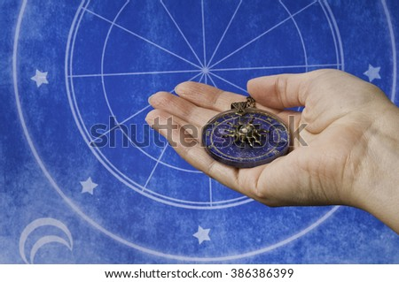 hand holding an astrological medallion  - stock photo