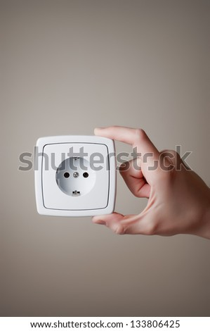 Hand holding an electric outlet - stock photo