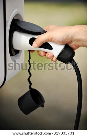 Hand holding an electric plug in for charging electric car - stock photo