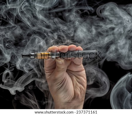 Hand holding an electronic cigarette over a dark background - stock photo
