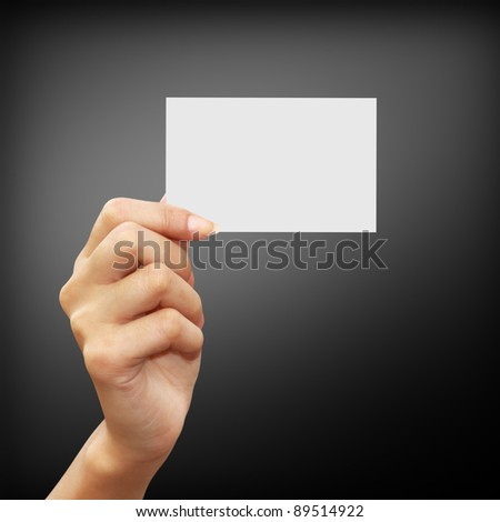 Hand holding an empty business card on black background - stock photo