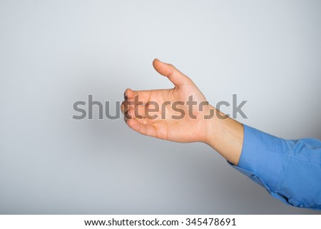 hand holding an invisible phone or cup. advertising or business concept, isolated on a gray background. - stock photo