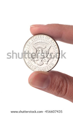 Hand holding an 1968 Kennedy Half Dollar Value coin isolated on white background. Old coin.