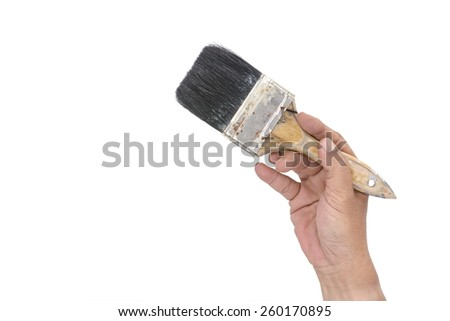 Hand holding an old dirty used paint brush isolated on a white background