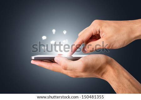 Hand holding and touching smart phone with blank screen with social icons, side view on dark background.