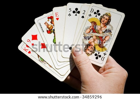hand holding anglo-american playing cards isolated on black - stock photo