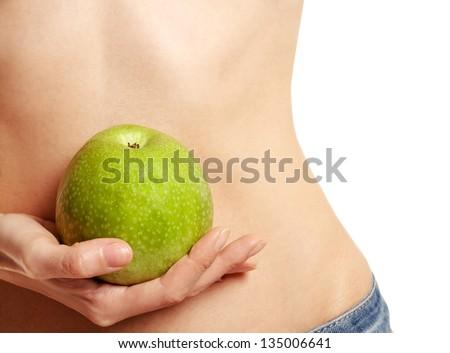 Hand holding apple at waist level - stock photo