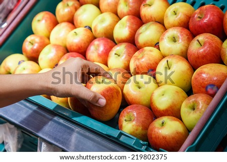 Hand holding apple in department store